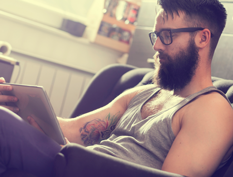 a bearded tattooed man using a tablet